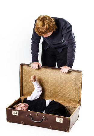 Two red-haired brothers playing with vintage suitcase photo