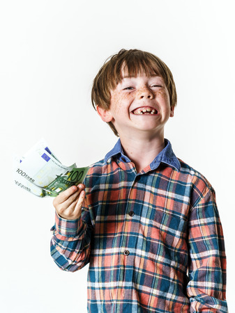 luckiness: Happy red-haired boy with money in his hand