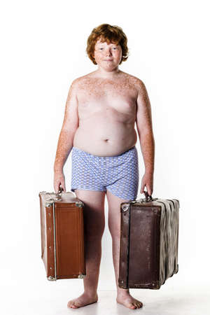undressed: Undressed poor red-haired boy with old suitcases isolated on white