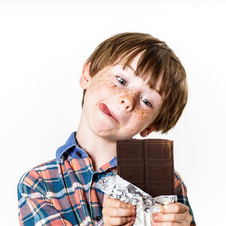 Happy red-haired boy with chocolate bar isolated on white Standard-Bild