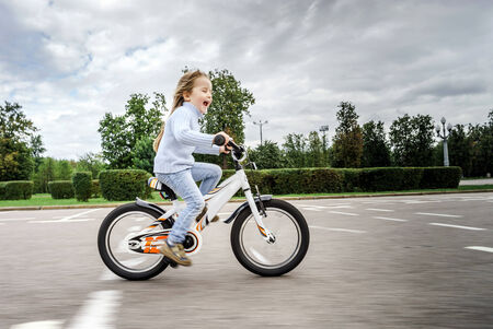 Cute little girl riding fast by bicycle in public park