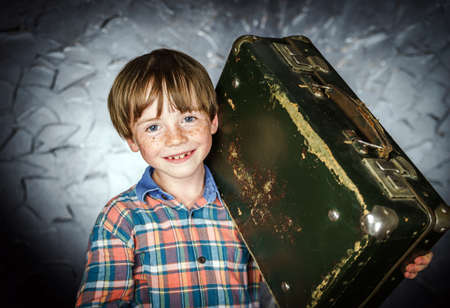 laughable: Emotional red-haired boy with retro vintage suitcase