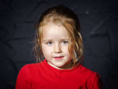 Cute little girl in red jacket isolated on black photo
