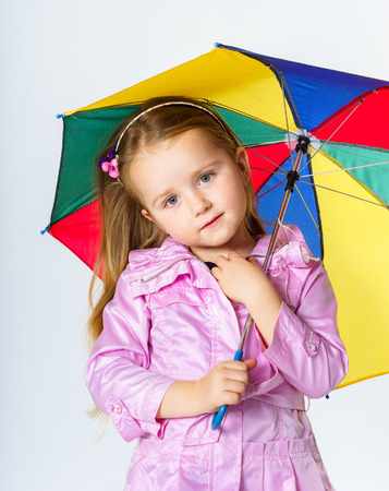 Cute little girl with colorful umbrella isolated on white background photo
