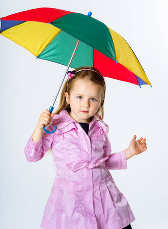 Cute little girl with colorful umbrella isolated on white bachground photo