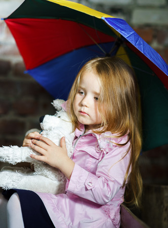 Cute little girl with colorful umbrella and lovely toy photo