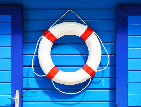 flotation: White flotation ring on the blue wall near boat rental