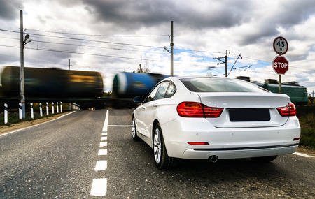 super highway: Luxury white car waiting for train  at the railway crossing
