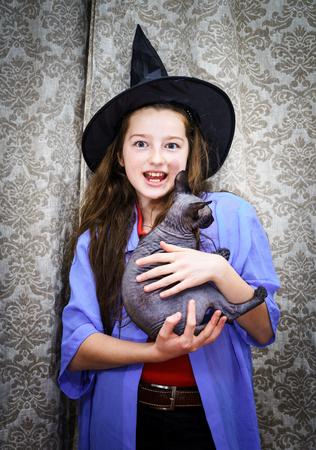 jeune fille adolescente nue: Adolescente en costume de sorcière avec Sphynx Banque d'images