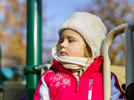 jumpers: Cute little girl dressed in pink jumpers on child playground, october sunny day