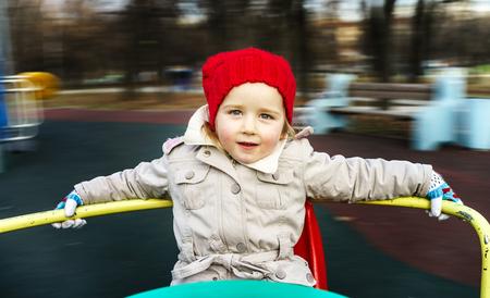 turnaround: Cute little girl rounding on merry-go-round, carrousel on child playground