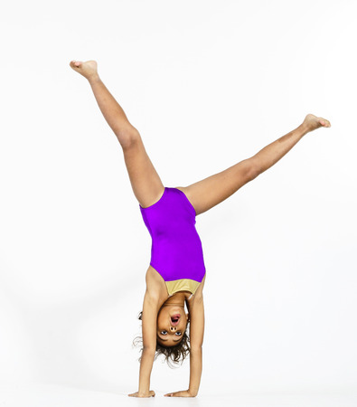 Young cute afro-american girl doing gymnastics isolsted on white background