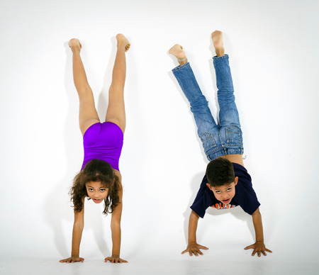 Young active afro-american children doing gymnastics isolsted on white background
