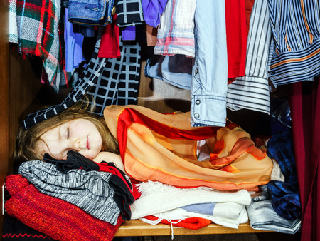 lurk: Cute little girl hiding inside wardrobe from her parents early morning