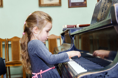 piano lesson: Cute little girl playing grand piano in music school Stock Photo