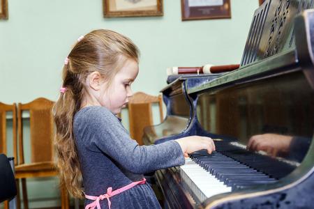 tocando piano: Ni�a linda que juega piano de cola en la escuela de m�sica