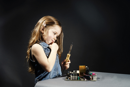 remount: Cute little girl helping father to repair old computer motherboard using solderer