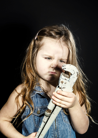 Cute little girl with gas spanner in her hands ready to professional constructing work Stock Photo
