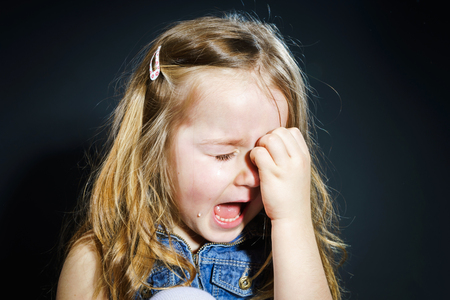 harmed: Crying cute little girl with focus on her tears on dark background