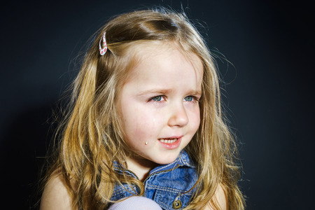 Crying cute little girl with focus on her tears on dark background