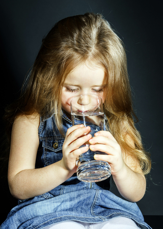 Cute little girl drinking clear water from glass photo