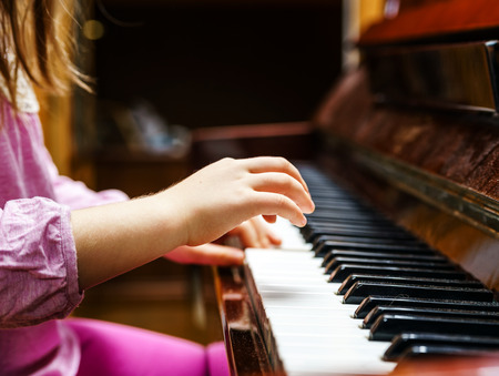 Little girl studing to play the piano at home photo