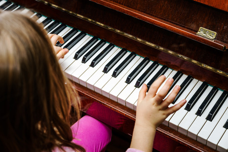 Little girl studing to play the piano at home