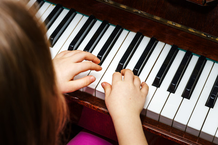 studing: Little girl studing to play the piano at home