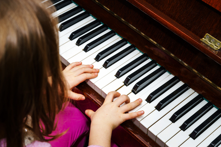 piano closeup: Little girl studing to play the piano at home