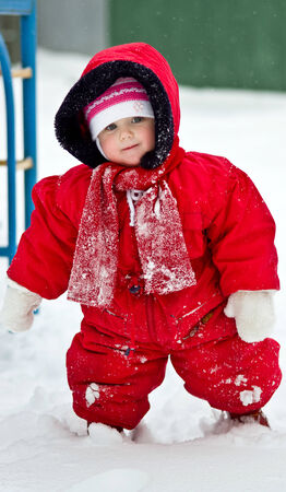 Cute little baby clothing in big jumpers in the snowy winter park