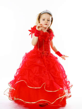 Cute little princess dressed in red  with crown on her head posing in studio. Children fashion. Stock Photo