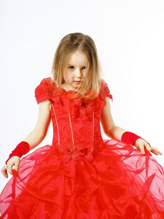 Cute little princess dressed in red dancing. Isolated on white background. Children fashion.