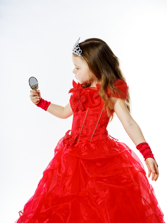 Cute little princess dressed in red looking to the compact mirror isolated on white background Stock Photo