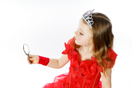 narcissism: Cute little princess dressed in red looking to the compact mirror isolated on white background Stock Photo
