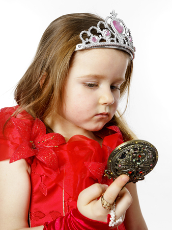 fandango: Cute little princess dressed in red looking to the compact mirror isolated on white background Stock Photo