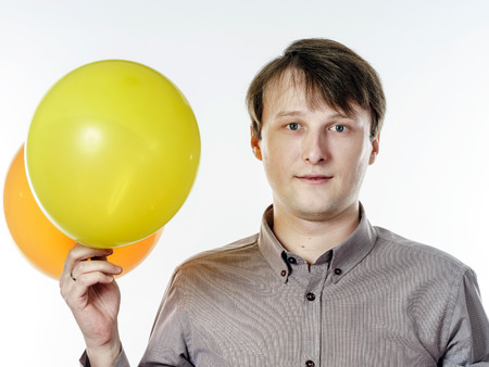 Young caucasian man holding yellow air balloons in his hand. Happy like a child. photo