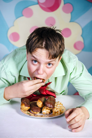 covetous: Funny teenage boy eating sweet cakes, hungry and candy man Stock Photo
