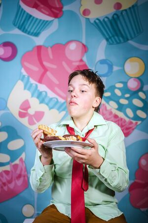 Funny teenage boy eating sweet cakes, hungry and candy man Stock Photo