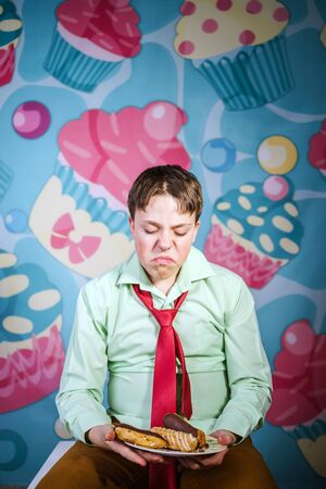 avid: Funny teenage boy eating sweet cakes, hungry and candy man Stock Photo