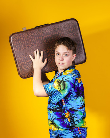 Affective teenage boy with retro suitcase isolated on yellow