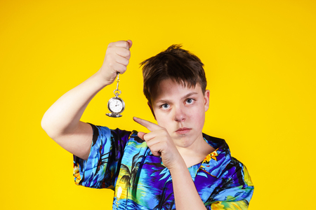 Affective teenage boy with watch showing time, isolated on yellow, concept Banque d'images