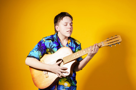 Affective teenage boy with guitar. Music concept. Isolated on yellow background