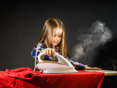striping: Cute little girl helping your mother by ironing clothes, childhood concept