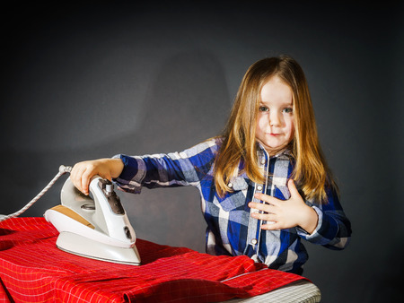 helpmate: Cute little girl helping your mother by ironing clothes, childhood concept