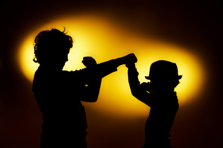 emphatic: Two  expressive boys silhouettes showing emotions using gesticulation, isolated on yellow Stock Photo