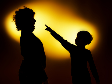 eloquent: Two  expressive boys silhouettes showing emotions using gesticulation, isolated on yellow Stock Photo