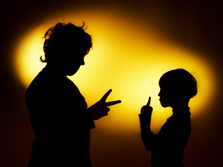 gesticulation: Two  expressive boys silhouettes showing emotions using gesticulation, isolated on yellow Stock Photo
