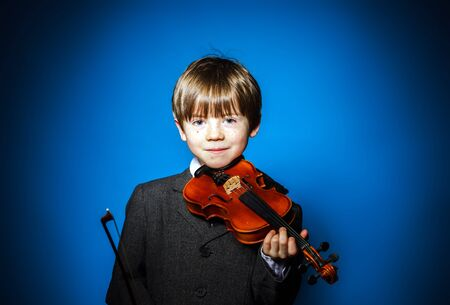 eloquent: Red-haired preschooler boy with violin, isolated on blue, music concept