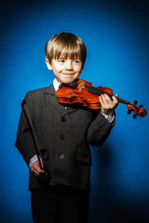 ruffian: Red-haired preschooler boy with violin, isolated on blue, music concept