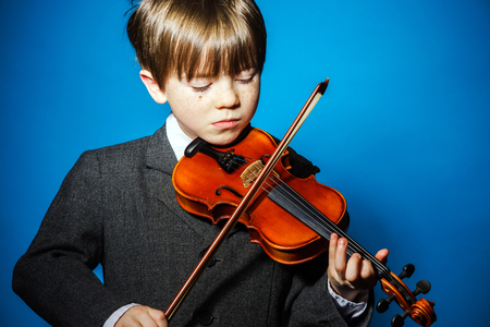 emphatic: Red-haired preschooler boy with violin, isolated on blue, music concept